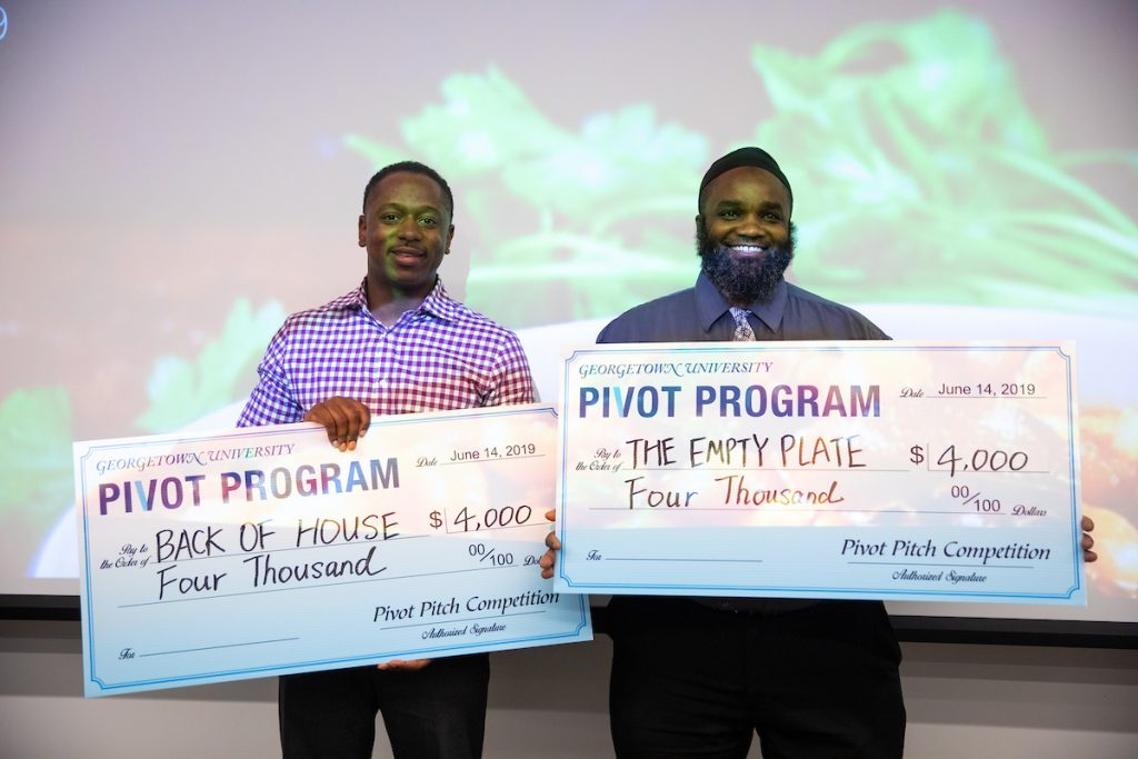 Two Pivot Fellows smiling and holding large checks.
